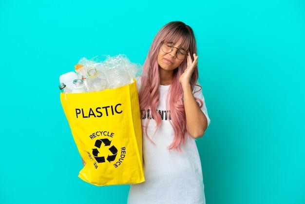 Giovane donna con i capelli rosa che tiene una borsa piena di bottiglie di plastica da riciclare isolata su sfondo blu con mal di testa
