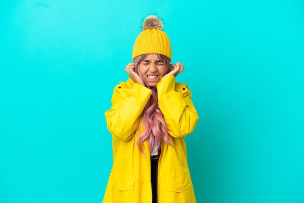 Giovane donna con i capelli rosa che indossa un cappotto antipioggia isolato su sfondo blu frustrato e che copre le orecchie