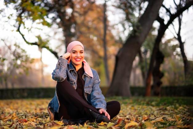 Giovane donna con una sciarpa rosa in testa nel parco