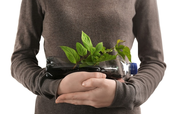 Giovane donna con bottiglia di plastica utilizzata come contenitore per la coltivazione di piante contro la luce