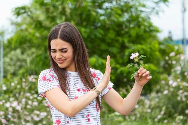 Giovane donna con allergia ai pollini che tiene un fiore e dice no ..