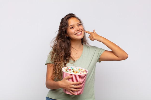 Giovane donna con un secchio pop conrs che sorride fiduciosamente indicando il proprio ampio sorriso, atteggiamento positivo, rilassato e soddisfatto