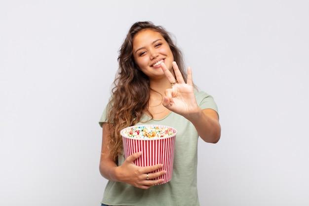 Giovane donna con un secchio pop conrs sorridente e guardando amichevole, mostrando il numero due o secondi con la mano in avanti, conto alla rovescia