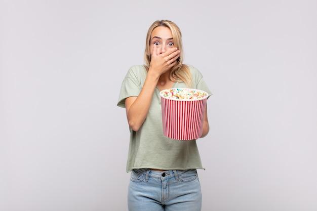 Giovane donna con un secchio di pop corn che copre la bocca con le mani con un'espressione scioccata e sorpresa, mantenendo un segreto o dicendo oops