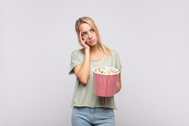 Giovane donna con un secchio per pop corn che si sente annoiata, frustrata e assonnata dopo un compito noioso, noioso e noioso, tenendo la faccia con la mano