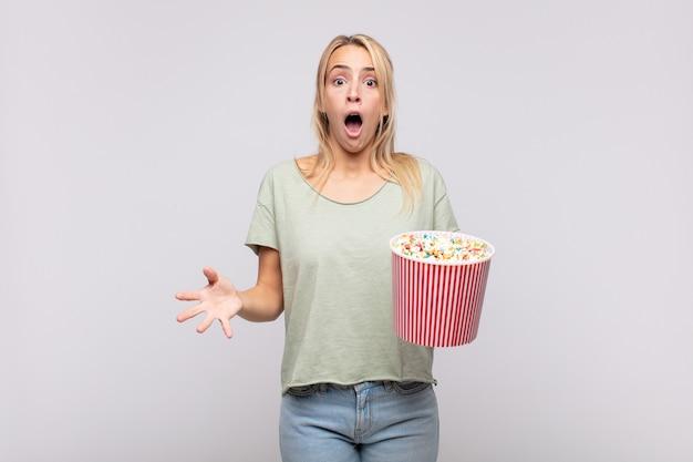 Giovane donna con un secchio per pop corn che si sente estremamente scioccata e sorpresa, ansiosa e in preda al panico, con uno sguardo stressato e inorridito