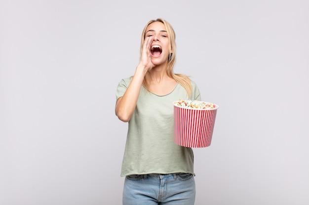 Giovane donna con un secchio di pop corn che si sente felice, eccitata e positiva