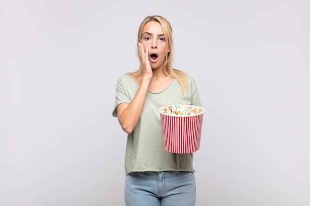 Giovane donna con un secchio per pop corn che si sente scioccata e spaventata, sembra terrorizzata con la bocca aperta e le mani sulle guance