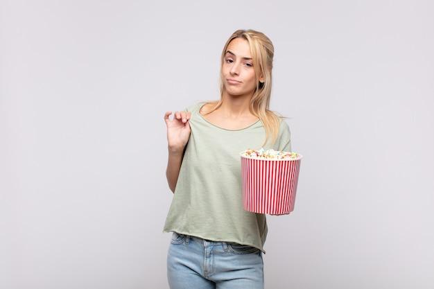 Giovane donna con un secchio di pop corn che sembra arrogante, di successo, positiva e orgogliosa, indicando se stessa