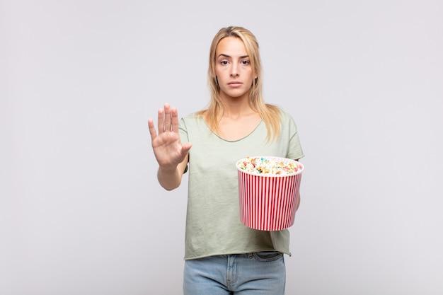 Giovane donna con un secchio di pop corn che sembra serio, severo, dispiaciuto e arrabbiato mostrando il palmo aperto che fa il gesto di arresto