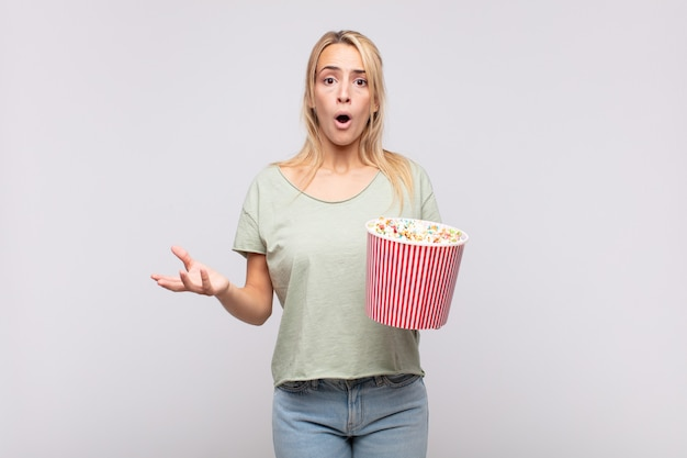 Giovane donna con un secchio per pop corn a bocca aperta e stupita, scioccata e stupita da un'incredibile sorpresa