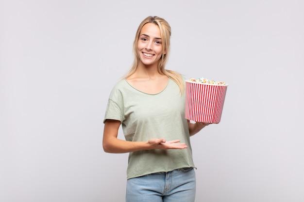 Giovane donna con un secchio di pop corn sorridendo allegramente, sentendosi felice e mostrando un concetto nello spazio della copia con il palmo della mano