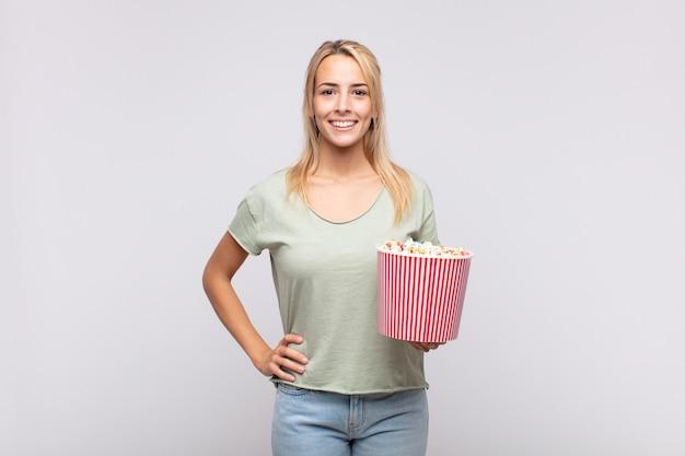 Giovane donna con un secchio di pop corn sorridendo felicemente con una mano sul fianco e atteggiamento fiducioso, positivo, orgoglioso e amichevole