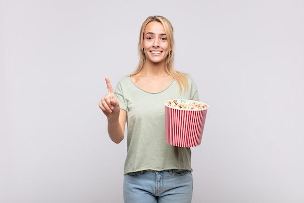 Giovane donna con un secchio di pop corn sorridendo e guardando amichevole, mostrando il numero uno o il primo con la mano in avanti, il conto alla rovescia