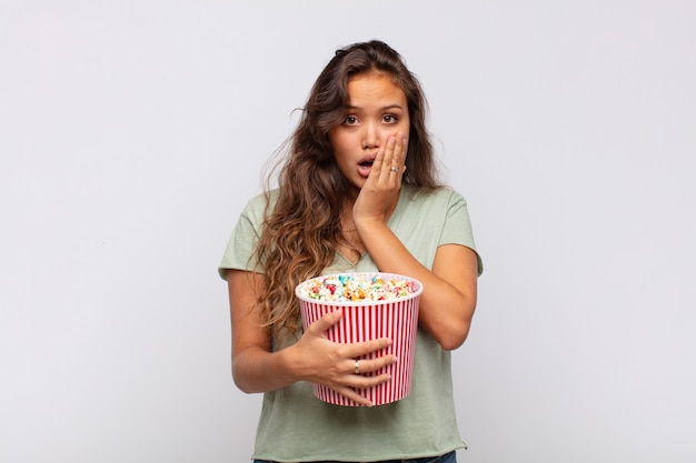 Giovane donna con un secchio di popcorn che si sente scioccata e spaventata, sembra terrorizzata con la bocca aperta e le mani sulle guance