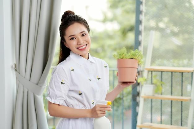 Giovane donna con piante in vaso su un balcone giardino. la floricoltura è un hobby.