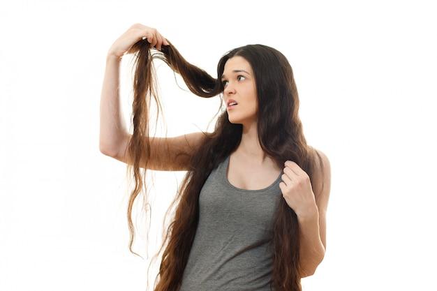 Giovane donna con problemi di capelli. su bianco isolato