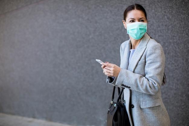 Giovane donna con maschera protettiva per il viso sulla strada