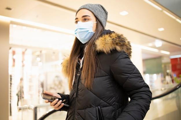 Giovane donna con una maschera protettiva di prendere le scale in un centro commerciale