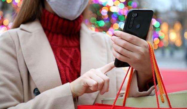 Giovane donna con maschera protettiva utilizza lo smartphone per lo shopping online e il trasporto di borse nel periodo natalizio