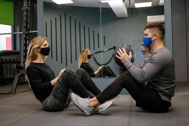 Giovane donna con maschera protettiva che lavora con personal trainer in palestra durante la pandemia covid-19. sta pompando il suo muscolo con il manubrio. focalizzazione morbida