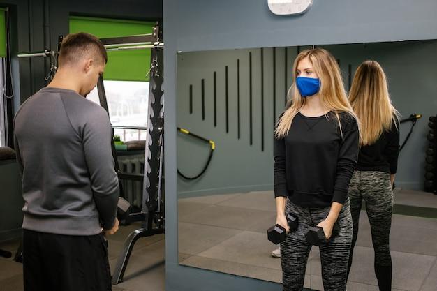 Giovane donna con maschera protettiva che lavora con personal trainer in palestra durante la pandemia covid-19. sta pompando il suo muscolo con il manubrio.