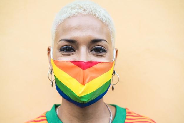 Giovane donna con la maschera di gay pride bandiera arcobaleno