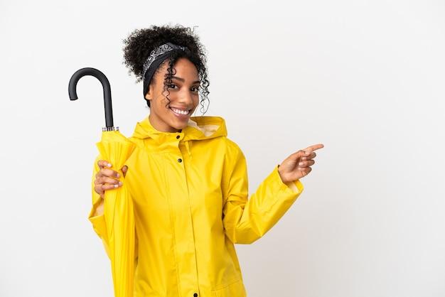 Giovane donna con cappotto antipioggia e ombrello isolato su sfondo bianco che punta il dito a lato