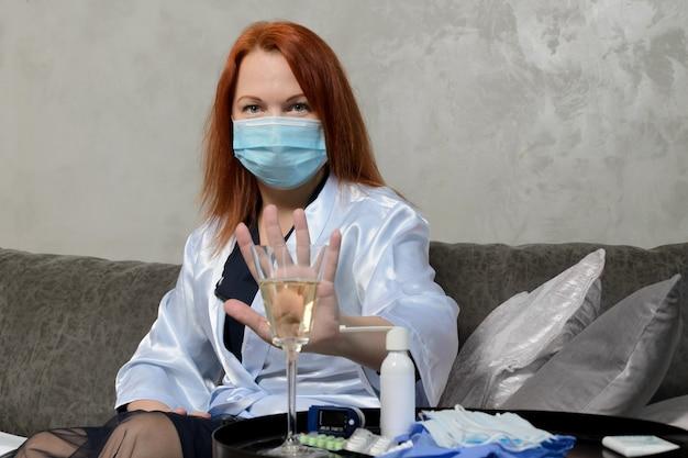 La giovane donna con i capelli rossi nella mascherina medica mostra il gesto di rifiuto di un bicchiere di champagne.
