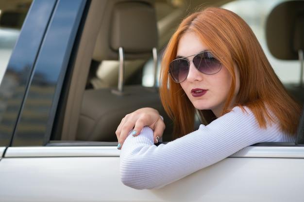 Giovane donna con i capelli rossi e occhiali da sole che viaggiano in auto. passeggero guardando fuori dal lunotto di un taxi in una città.