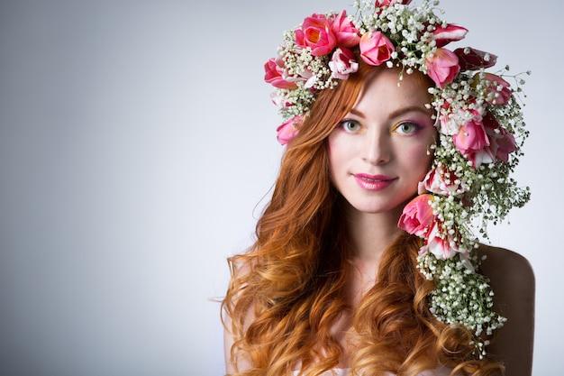 Giovane donna con i capelli rossi che indossa una corona di tulipani