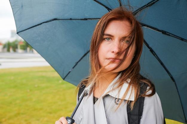 Giovane donna con i capelli rossi con l'ombrello