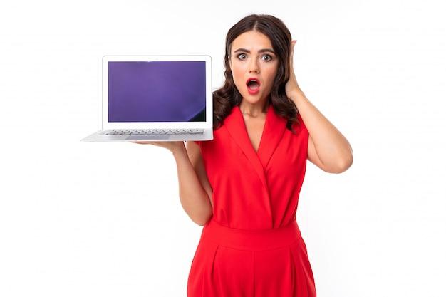 Una giovane donna con labbra rosse, trucco luminoso, lavora con un computer portatile bianco ed è scossa da qualcosa sullo schermo, immagine isolata
