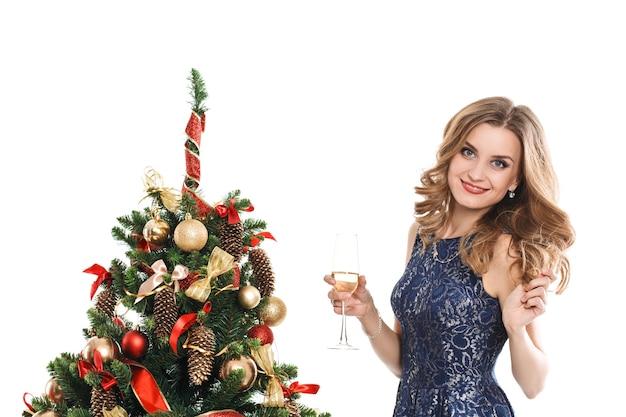 Giovane donna con labbra rosse, tenendo un bicchiere di champagne vicino all'albero di natale