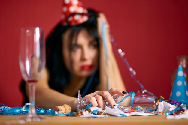 Giovane donna con rossetto rosso strofinato e berretto, seduta stanca al tavolo nella stanza disordinata dopo la festa di compleanno, donna dopo la festa a casa