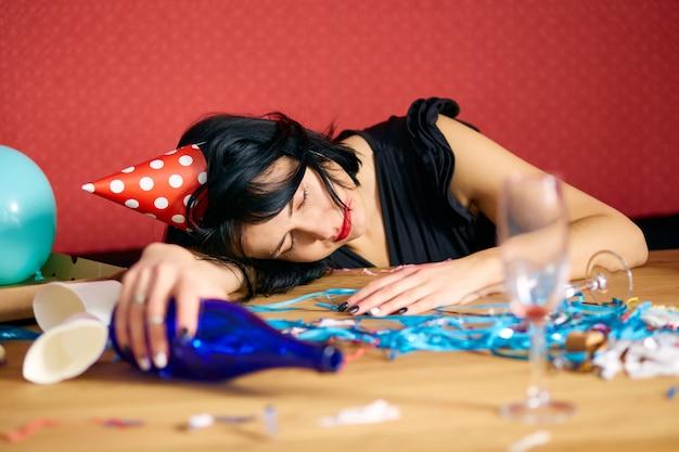 Giovane donna con rossetto rosso strofinato e cappuccio, che dorme a tavola nella stanza disordinata dopo la festa di compleanno, donna stanca dopo la festa a casa