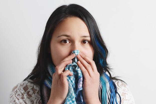 Giovane donna con un naso che cola usa un fazzoletto