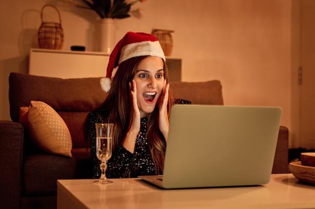 Giovane donna con il cappello di babbo natale che fa una videochiamata alla sua famiglia per festeggiare il natale.