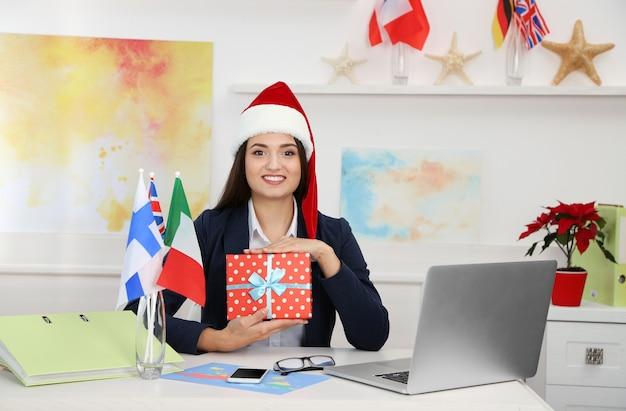 Giovane donna con cappello da babbo natale che mostra una confezione regalo nell'ufficio della compagnia di viaggi