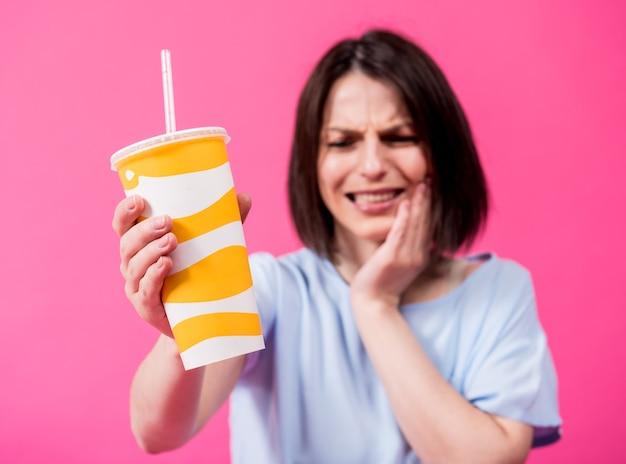 Giovane donna con denti sensibili che beve acqua fredda su sfondo colorato