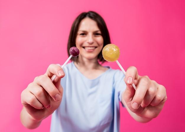 Giovane donna con denti sensibili che mangia lecca-lecca dolce su sfondo a colori