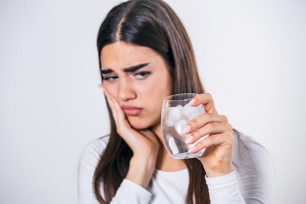 Giovane donna con denti sensibili e mano che tiene un bicchiere di acqua fredda con ghiaccio.