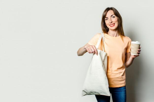 La giovane donna con un sacchetto della spesa e tiene una tazza di carta con caffè su un fondo leggero
