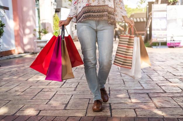 Giovane donna con i sacchetti della spesa al centro commerciale il venerdì nero, concetto di stile di vita della donna