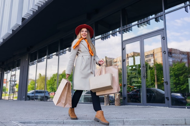 Giovane donna con le borse della spesa camminando sulla strada della città