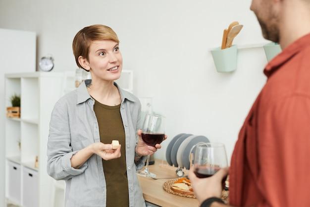Giovane donna con i capelli corti, bere vino rosso e mangiare formaggio e parlare con l'uomo mentre sono in cucina