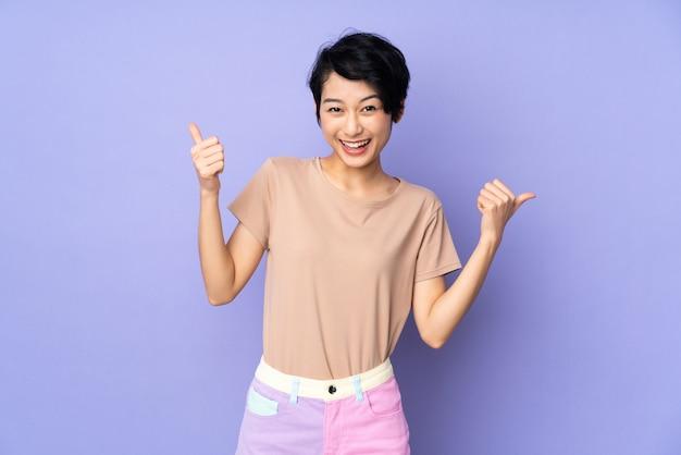 Giovane donna con i capelli corti sopra viola isolato dando un pollice in alto gesto