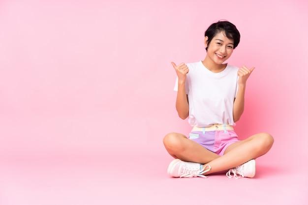 La giovane donna con i capelli corti che si siede sul pavimento sopra la parete rosa con i pollici aumenta il gesto e sorridere
