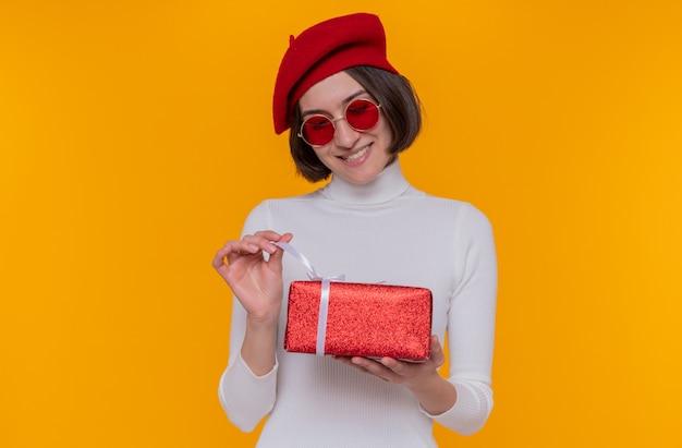 Giovane donna con i capelli corti in dolcevita bianco che indossa berretto e occhiali da sole rossi tenendo un presente felice e allegro andando ad aprire presente sorridendo allegramente