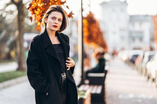 Giovane donna con taglio di capelli corto e labbra rosse che passeggiano per le strade della città